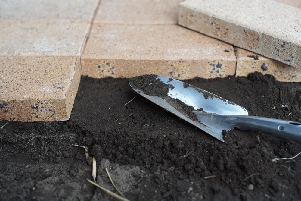 小屋脇にレンガを敷く 土を盛りながら調整